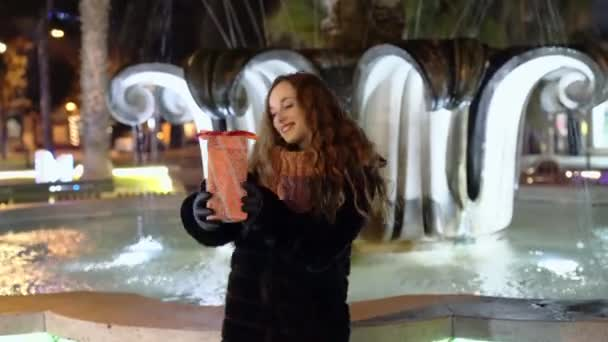 Pretty smiling woman dancing in the park with christmas gift in hands, happy female enjoying winter night walking in the park with marble fountains. Real emotion of happiness and joy, christmas