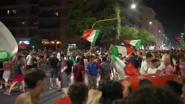 ŘÍM, ITÁLIE - 11. června 2021: Italští fanoušci s vlajkami blokujícími silnice po vítězství fotbalového týmu v UEFA EURO 2020, šťastní pouliční fanoušci tančící na cestách, skákající a jásající radostí