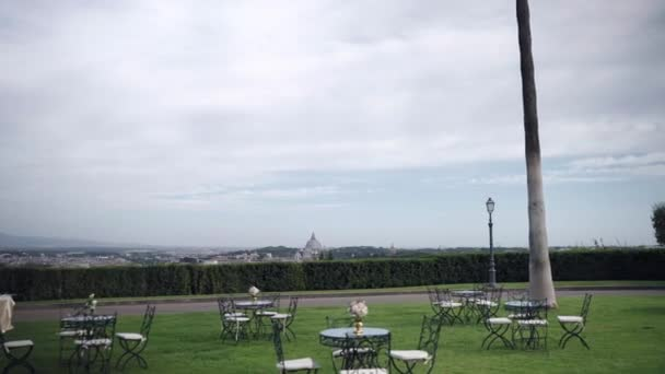 Luxury wedding celebration outdoors on Italian ancient noble villa with amazing view on majestic Vatican Dome, trendy decorations for table settings in the garden, festive decor preparation for night
