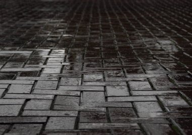 Wet black brick road after heavy rainfall