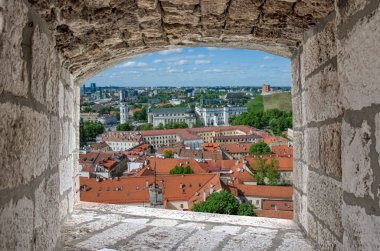 View from stone window of city center in Vilnius, Lithuania.  View from above of St. Stanislaus Cathedral on Cathedral Square, Gediminas castle on the hill, red rooftops.