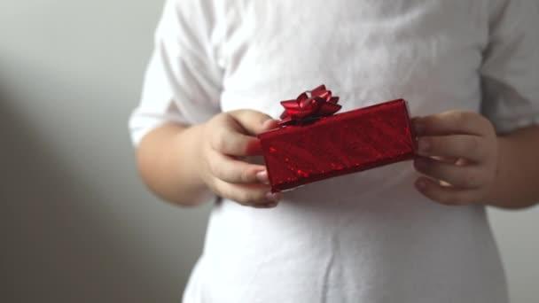 A fiú piros ajándékot ad Valentin-napra. Karácsonyi ajándék.