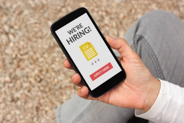 Hand holding smartphone with we are hiring apply now concept on