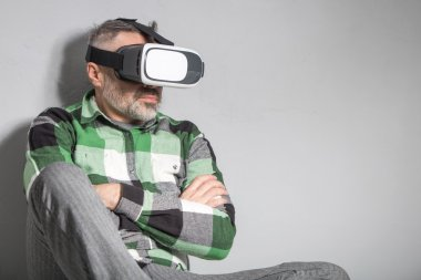 Man in virtual reality glasses over grey background