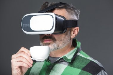 Man in virtual reality glasses over grey