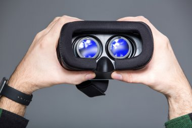 Virtual glasses in man hands over grey