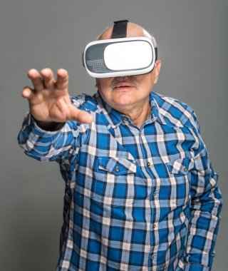 Old man in virtual reality glasses have fun