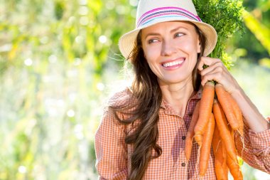 Woman with organic carrots in a vegetable garden