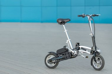 Folding electric bike outdoors on blue and grey