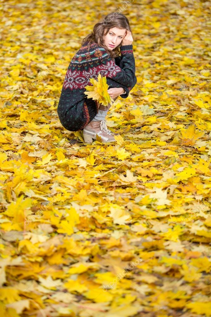 Fall Fashion. Autumn woman in park in knitted autumn clothes over yellow  leaves around