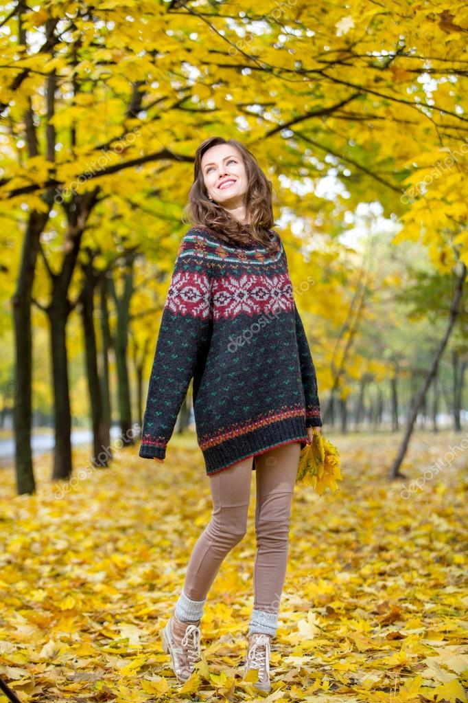 Autumn woman in park in knitted autumn clothes