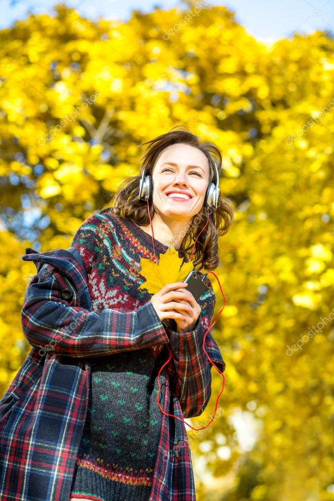 Beautiful girl listening to music in autumn yellow park