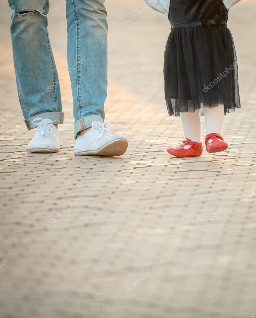 aff5851237 Padre de piernas en jeans rotos y su hija niña de zapatos rojos — Foto de