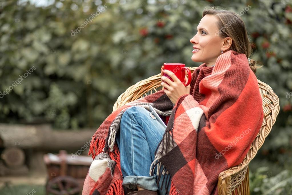 Beautiful girl drinking coffee in autumn garden