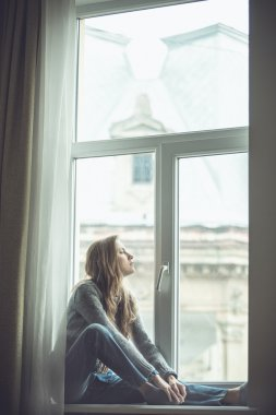 Beautiful young woman sitting by the window
