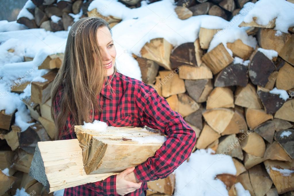 young woman posing with wooden logs for bonfire