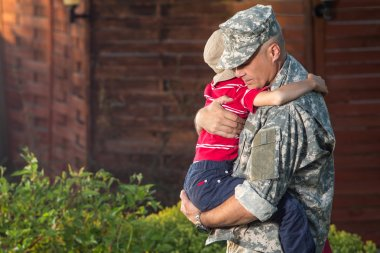 Military man father hugs son