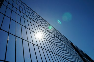 Wired fence over sky