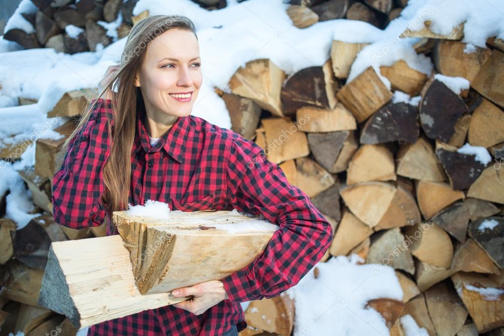 young woman posing with wooden logs