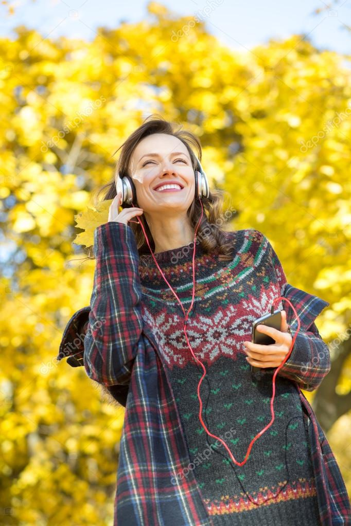Beautiful girl listening to music in autumn landscape golden park