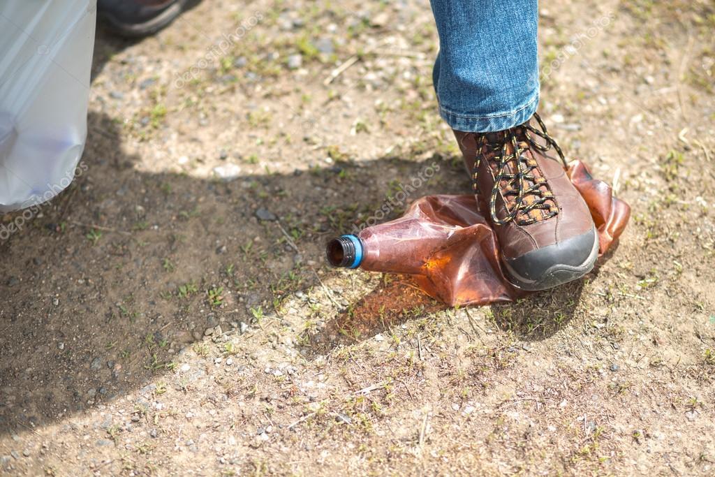 Woman picking up trash, focus on shoe