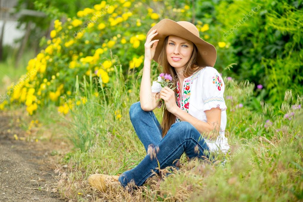 Happy woman sitting on rural road with yellow roses background