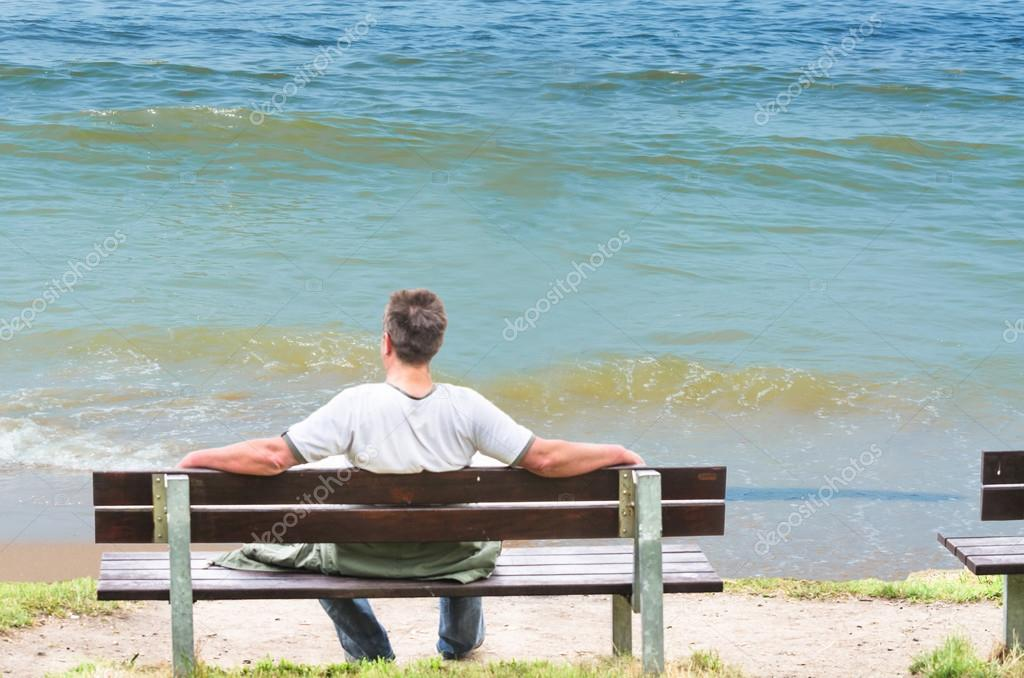 Man on bench, looking out to sea