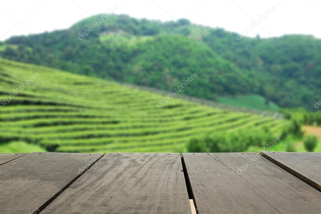 Perspective wood over blur beautiful tea faem and landscape mountain hill for background usage