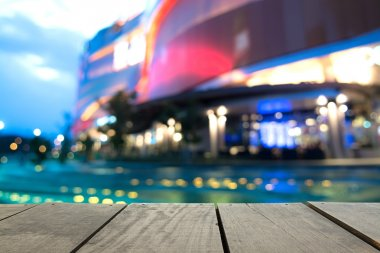 Defocus and blur image of terrace wood and swimming pool in  modern hotel for background usage