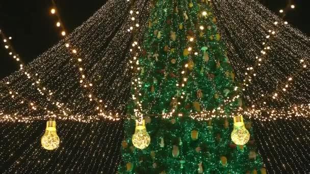 Weihnachtsbaum mit Girlanden und dekorativen Lampen geschmückt.