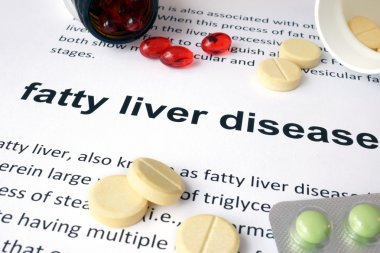 Paper with fatty liver disease  and pills.