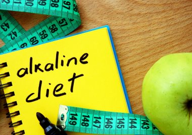 Notepad with alkaline diet, apple and measure tape