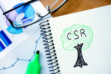 Notepad with  csr  Corporate social responsibility  on office wooden table.