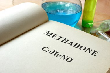 Book with methadone  and test tubes on a table.