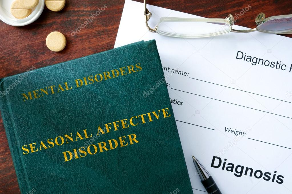 Seasonal affective disorder concept. Diagnostic form and book on a table.