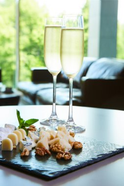 two glasses of champagne with a tray cheese