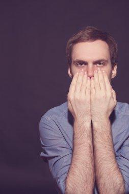 Speak no evil concept - Face of men covering his mouth.