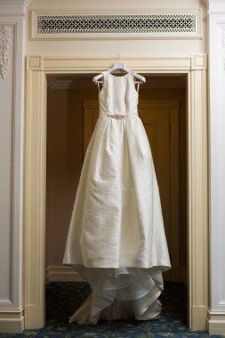 Wedding dress hanging up by the door stock vector