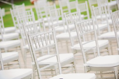 Prior to a wedding ceremony, endless white chairs