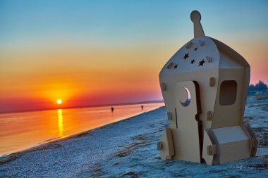 Cardboard toy spaceship at sea coast and sunset.