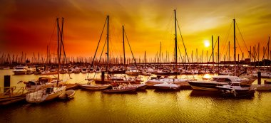 Sailing boats at harbor at orange sunset in La Rochelle, France