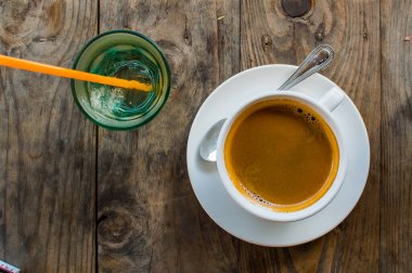 Strong and dark coffee in a white porcelain cup served with a glass of water on a side on a wooden table outdoors in cafe