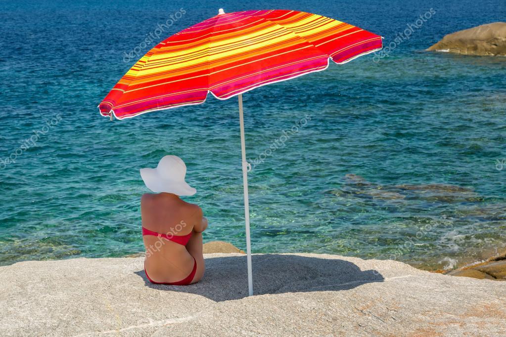 Grote Witte Parasol.Vrouw In Rode Bikini En Witte Hoed Onder Parasol Uitkijken Naar S