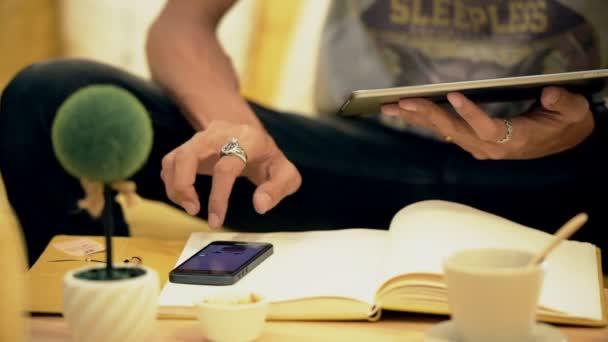 Mladý muž pití kávy v kavárně a pomocí telefonu a tabletu