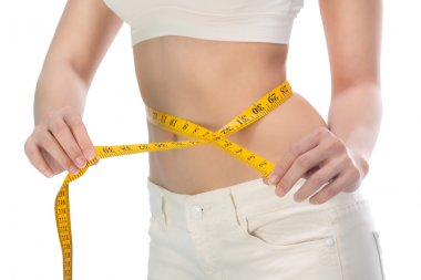 healthy lifestyles concept Woman measuring toned waist.