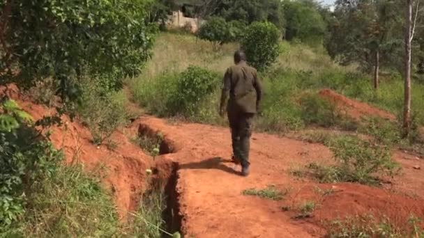 Black Man in Green Clothes Walks in Africa Nature. Village one solo single people male alone walking walk African red soil back nature soldier army ranger Nigeria Congo Tanzania South Africa Kenya 4K