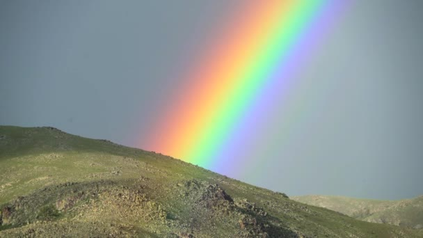 Dense Rainbow in treeless hill.Powerful hard dark curved colored colorful weather air meteorology background circle grassland prairie meadowpasture plateau tableland lowland plain sky spectrum sunlight majestic beauty wonderful excellent amazing best
