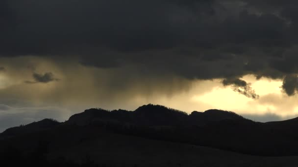 Rains on the mountains at sunrise.Weather mount mountainous montane higher elevation terrain geography rain rains raining precipitation downfall curtain of rain microburst downburst torrential time lapse cinematic background landscape view nature 4K.