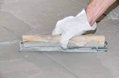 Tiler filling up joints with a rubber squeegee