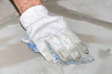 Tiler cleaning tiles after filling up joints